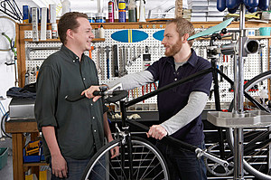 Two young men having conversation while repairing bike in bicycle shop